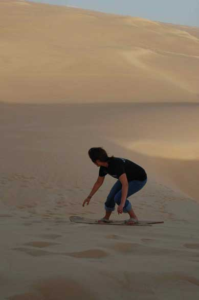 A woman sandboarding on the golden dunes of the Great Sand Sea near Bir Wahed. Photo: Mariya Karimjee.