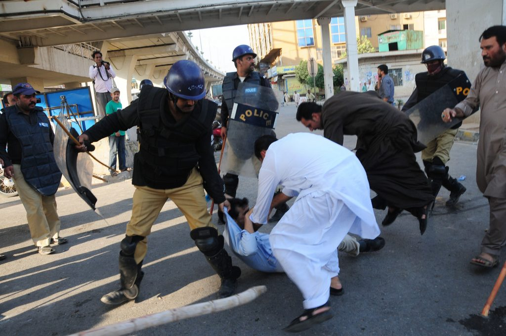 Pakistani policemen arrest an activist of Pakistan Tehreek Insaaf