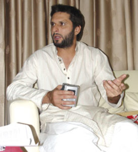 A cricketer and a gentleman: Shahid Afridi holds the tape recorder for Newsline's Farieha Aziz, ensuring that she has a clear record of every word from the interview performed at his Karachi home in April 2011. Photo: Saif Karamali