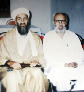 Journalist Rahimullah Yusufzai (right) sits with Osama bin Laden for a photo after conducting an interview with the infamous militant in Afghanistan in 1998.