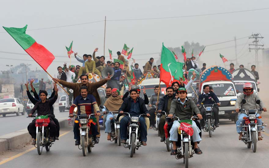 Activists of Pakistan Tehreek-e-Insaaf (PTI) arrive to attend a protest rally in Peshawar on November 23, 2013. Thousands of Pakistani activists from right-wing political parties November 23 protested against US drone strikes, threating to block NATO supply routes, if strikes continue. AFP PHOTO/A MAJEED