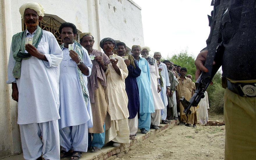 Pakistani men display their identification cards as they stand in a queue to vote in a by-election for a seat in the national parliament, in Tharpakar, Sindh province, 18 August 2004, as policeman stands guard. Shaukat Aziz, the finance wizard chosen by President Pervez Musharraf to be Pakistan's next prime minister, sought to cut a path to the parliament's lower house through a virtually guaranteed by-election in this rural seat. AFP PHOTO/Asif HASSAN