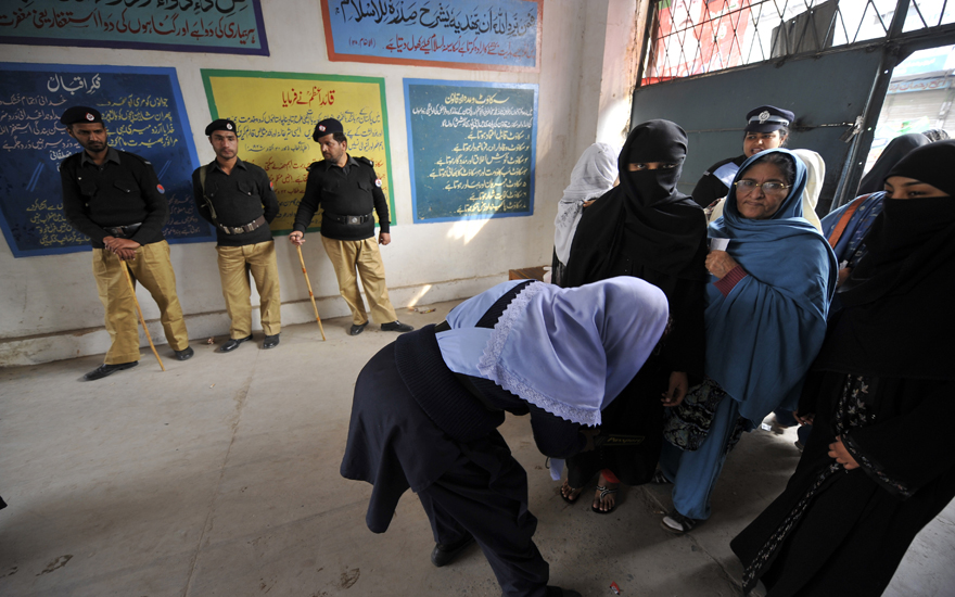 A Pakistani police officer searches women entering a polling station during a by-election in Rawalpindi on February 24, 2010. More than 20 candidates contested in the by-election to fill the seat which fell vacant after the resignation of an MP from Rawalpindi, just outside the Pakistani capital Islamabad. The Pakistan People's Party (PPP) of assassinated former premier Benazir Bhutto came into power after winning the general elections in February 2008. AFP PHOTO/ AAMIR QURESHI