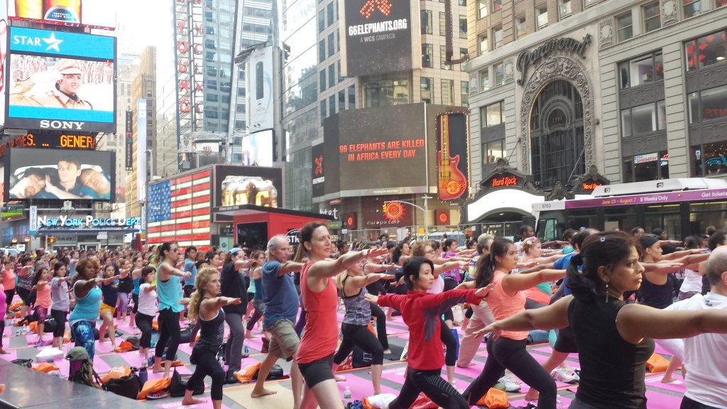 People perform yoga exercises on June 20, 2016 on Times Square in New York City. Yogis from throughout the world travel every year to Times Square to celebrate the Summer Solstice with free yoga classes in the heart of New York City, on what is the Northern Hemisphereís longest day of the year. / AFP PHOTO / Brigitte DUSSEAU
