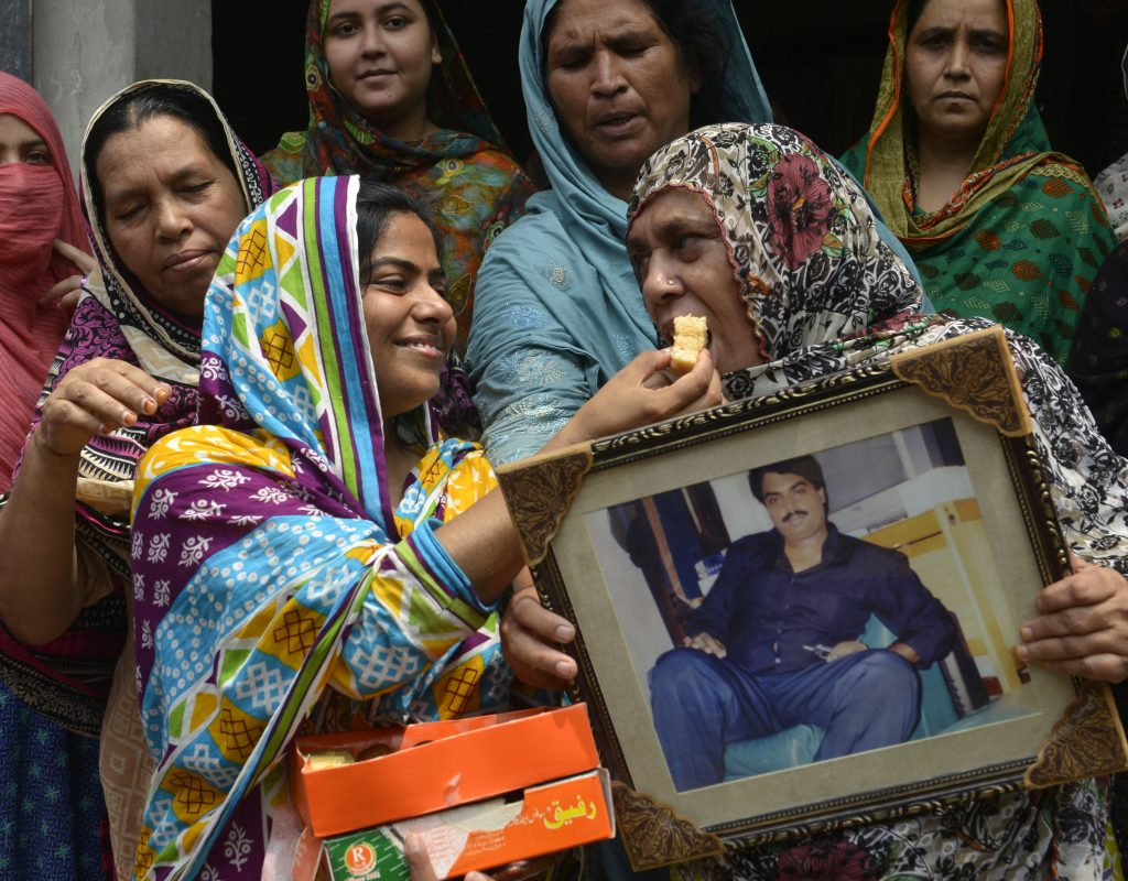 "Relatives of Pakistani national, Zulfiqar Ali, who was convicted to death in 2005 for heroin possession, hold his photograph as they share sweets in celebration after the Indonesian government halted his execution, in Lahore on July 29, 2016. Indonesia executed four drug convicts July 29, but 10 others due to face the firing squad were given an apparent reprieve in a confused process one lawyer condemned as a ""complete mess"". The first reprieved was Pakistani Zulfiqar Ali, whom rights groups say was beaten into confessing to heroin possession, leading to his 2005 death sentence. / AFP PHOTO / ARIF ALI"