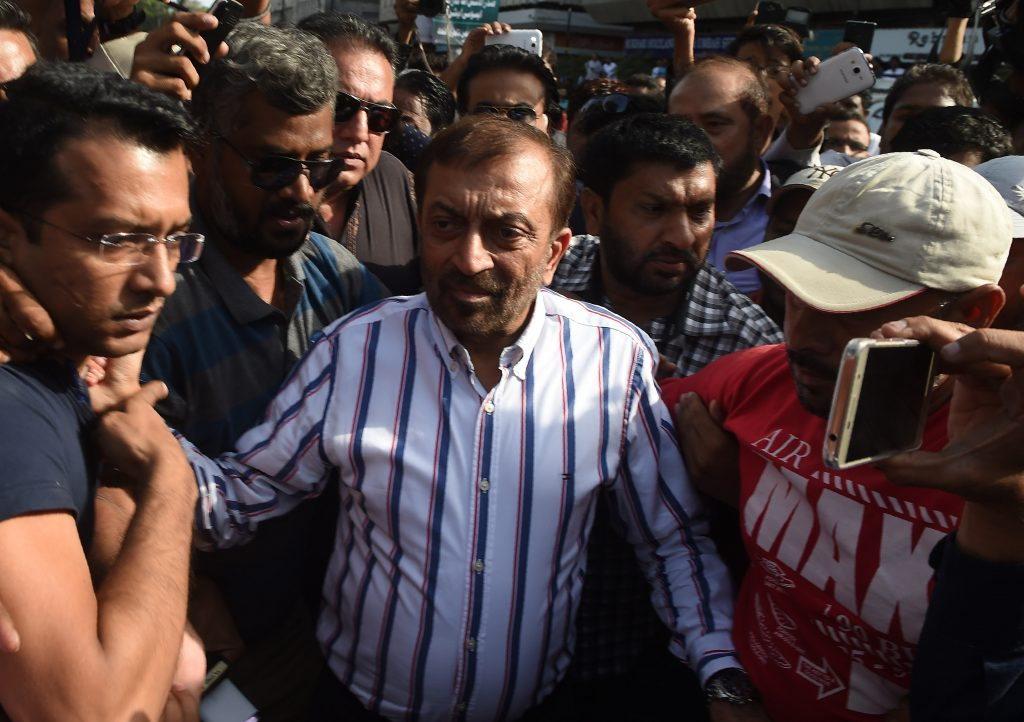 Pakistani Muttahida Qaumi Movement (MQM) political party leader Farooq Sattar (C) arrives for a press conference in Karachi on August 23, 2016. Pakistani police charged the exiled leader of an influential political party with treason and inciting terrorism Tuesday, accusing him of provoking violence at a protest a day earlier in Karachi. Altaf Hussain, leader of the Muttahida Qaumi Movement (MQM) which rules Karachi, Pakistan's biggest city, was accused with a dozen other party leaders of raising anti-Pakistan slogans at the demonstration on August 22, 2016. / AFP PHOTO / ASIF HASSAN