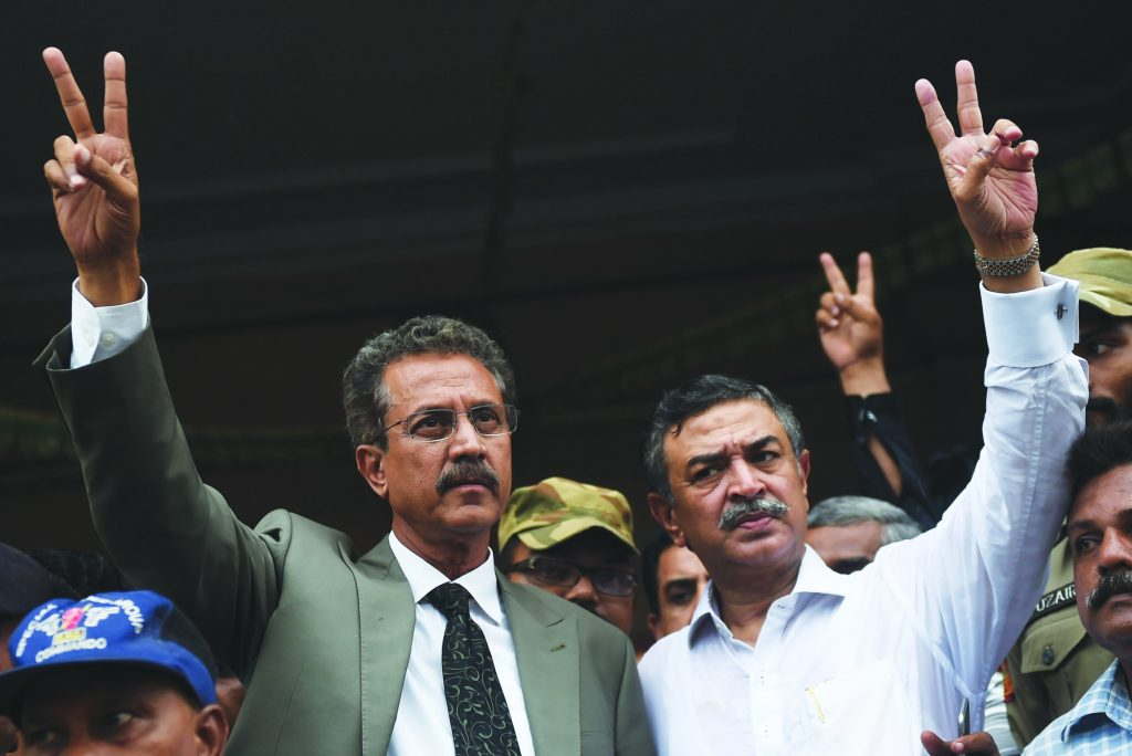 Newly elected mayor of Karachi of the influential Muttahida Qaumi Movement (MQM) party, Waseem Akhtar (L) and his deputy mayor Arshad Vohra flash victory signs after winning the mayoral election in Karachi on August 24, 2016. The Pakistani port megacity of Karachi on August 24 elected as mayor a politician who is currently in jail on sedition and terrorism charges, a day after the leader of his party was charged with treason. Waseem Akhtar, a former minister and parliamentarian of the influential Muttahida Qaumi Movement (MQM), won by a landslide with 196 of the total 294 votes cast by the city's municipal authorities. Akhtar was arrested in July 2016 and accused of ordering a crackdown on city riots in 2007, when he was serving as provincial home minister, that resulted in a bloody massacre. / AFP PHOTO / RIZWAN TABASSUM