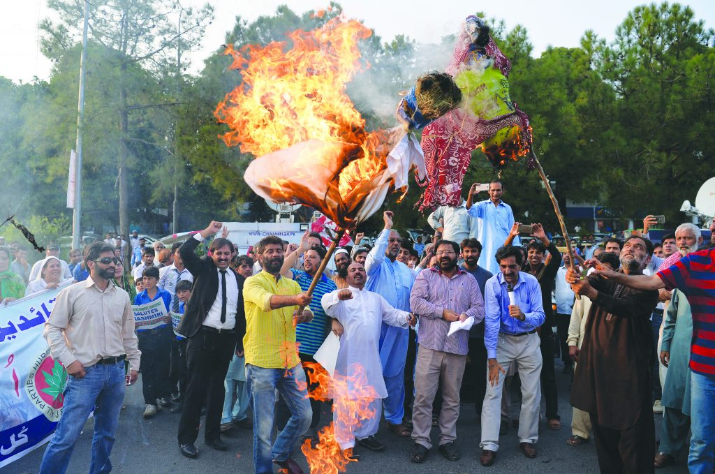 "Pakistani Kashmiris burn effigies of Indian Prime Minister Narendra Modi and Foreign Minister Sushma Swaraj during a protest in Islamabad, on September 26, 2016, to show their solidarity with Indian Kashmiri Muslims. Indian Prime Minister Narendra Modi lashed out at Pakistan last week accusing it of ""exporting terrorists"" after a deadly attack on an army base that New Delhi has blamed on Pakistan-based militants. Modi's comments were the latest in a war of words between the neighbours over escalating tensions in disputed Kashmir, where 18 Indian soldiers were killed last week in the worst attack in the region for over a decade. / AFP PHOTO / AAMIR QURESHI"