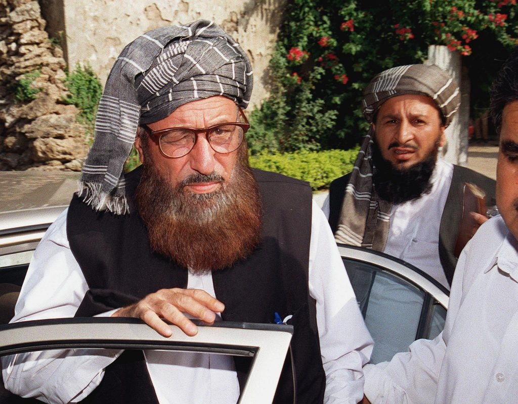 Maulana Samiul Haq (L), chairman of the council for the defence of Afghanistan, coming out of his car for a press conference in Rawalpindi, some 25km from Islamabad, 19 September 2001. Haq told the press conference that the council, which consists of several main religious parties, decided to mark protests across the country against the Pakistani government for its support of the US. Unidentified aid of Haq is at right. (FILM) AFP PHOTO