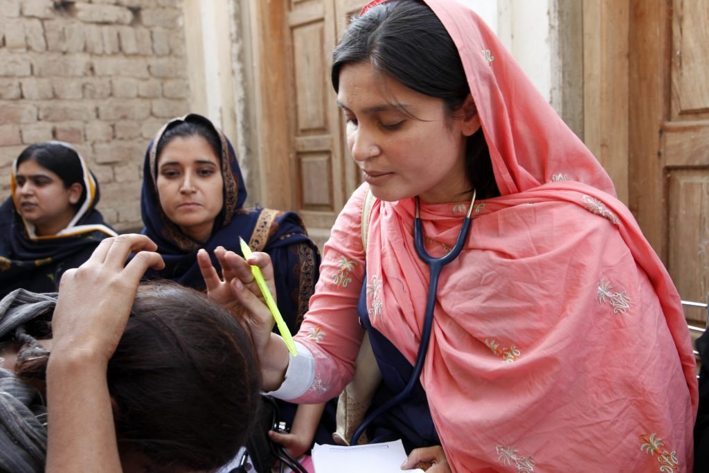 A female doctor with the International Medical Corps examines a woman patient at a mobile health clinic in the village of Goza, near Dadu in Pakistan's Sindh province. Funding from the UK government is enabling the International Medical Corps to operate mobile health clinics in Sindh, as part of the UK's response to the Pakistan floods. These clinics will provide access to basic healthcare services for thousands of people across Sindh as they return home to communities which were devastated by the floods in August 2010. The floods destroyed clinics and hospitals as well as homes and schools, so mobile teams of doctors, nurses and pharmacists are a vital way of reaching people in need of healthcare. The teams also operate as a disease 'early-warning' system; being getting out into the communities, they can spot the early signs of cholera and other water-borne diseases associated with large amounts of standing water and limited sanitation.